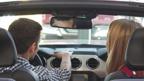 Gelukkig jong paar die vreugdevol het tonen van autosleutels aan hun nieuwe confertible glimlachen stock footage