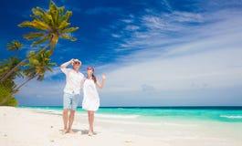 Gelukkig jong paar die in witte kleren door het strand lopen maldives Royalty-vrije Stock Foto's