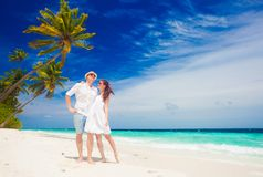 Gelukkig jong paar die in witte kleren door het strand lopen maldives Royalty-vrije Stock Foto