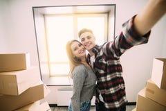 Gelukkig jong paar die zich aan nieuwe flat bewegen die selfie rond dozen nemen royalty-vrije stock afbeeldingen