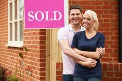 Gelukkig Jong Paar die zich naast Verkocht Teken buiten Nieuw Huis bevinden stock fotografie