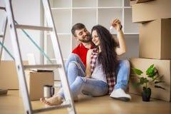 Gelukkig jong paar die zich in nieuwe huis uitpakkende dozen bewegen Royalty-vrije Stock Foto's