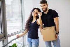 Gelukkig jong paar die zich in nieuwe huis uitpakkende dozen bewegen stock foto