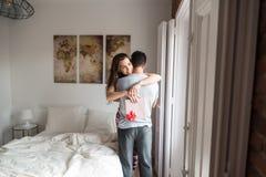 Gelukkig jong paar in liefde die elkaar met giften verrassen stock afbeeldingen