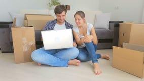 Gelukkig jong paar in liefde die op vloer situeren en nieuwe flat online kiezen stock footage