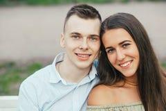 Gelukkig jong paar in liefdezitting op een parkbank en het koesteren Royalty-vrije Stock Afbeelding