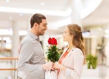 Gelukkig jong paar met bloemen in wandelgalerij Stock Afbeelding