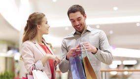 Gelukkig jong paar met het winkelen zakken in wandelgalerij stock video