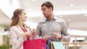 Gelukkig jong paar met het winkelen zakken in wandelgalerij stock footage