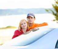 Gelukkig jong paar met hun nieuwe auto Royalty-vrije Stock Afbeeldingen
