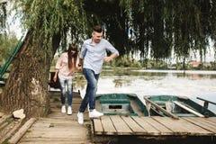 Gelukkig jong paar in openlucht jong liefdepaar die langs handen van een de houten brugholding lopen stock foto