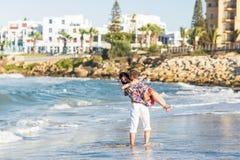 Gelukkig jong paar pret hebben, man en vrouw die in het overzees op een strand Royalty-vrije Stock Foto's