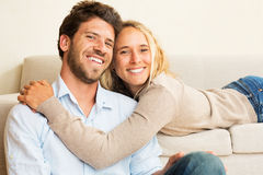 Gelukkig jong paar thuis op bank Royalty-vrije Stock Foto
