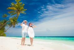 Gelukkig jong paar in witte kleren die pret hebben door het strand royalty-vrije stock fotografie