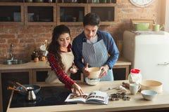 Gelukkig jong vrouw en man baksel in zolderkeuken royalty-vrije stock afbeelding