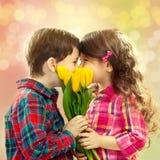 Gelukkig jongen en meisje met boeket van bloemen. stock afbeeldingen