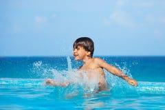 Gelukkig jongens bespattend water rond hem in pool royalty-vrije stock afbeelding