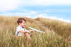 Gelukkig jongensspel met weinig wit vliegtuig royalty-vrije stock afbeeldingen