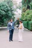 Gelukkig jonggehuwdepaar die in openlucht wanneer het lopen op de holdingshanden van de parksteeg samen en het lachen dansen Royalty-vrije Stock Foto