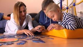 Gelukkig Kaukasisch familie het assembleren raadsel samen Man, vrouw en leuk weinig jongen die vrije tijd hebben thuis samen 4K stock video