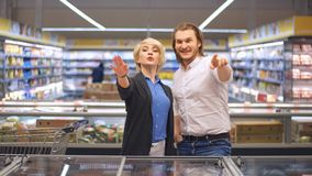 Gelukkig Kaukasisch paar die bevroren voedsel kiezen bij kruidenierswinkelopslag in winkelcomplex stock video