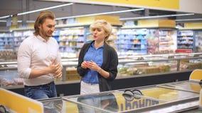 Gelukkig Kaukasisch paar die bevroren voedsel kiezen bij kruidenierswinkelopslag in winkelcomplex stock footage