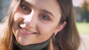 Gelukkig Kaukasisch vrouwelijk, camera bekijken en opzij, zijnd kalm en close-up lachen die geïsoleerd op stedelijk bevinden zich stock video