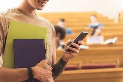Gelukkig kerel het typen bericht op smartphone in lezingszaal royalty-vrije stock foto