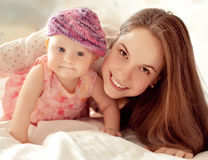 Gelukkig-kijkend baby die het breiende hoed en moeder spelen dragen Stock Fotografie