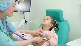 Gelukkig kind bij artsen` s ontvangst, overleg met ENT arts, otoscopie, raadsotolaryngoloog in kliniek, behandeling van stock footage