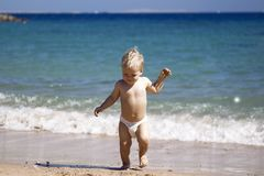 Gelukkig kind, de aanbiddelijke jongen van de blondepeuter in luier, die op het strand spelen die in het water lopen, die van oce Stock Afbeelding