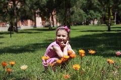 Gelukkig kind in de lentebloemen Royalty-vrije Stock Afbeeldingen