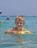 Gelukkig kind die in het overzees zwemmen Stock Foto