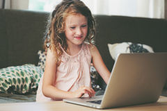 Gelukkig kind die laptop thuis met behulp van Schoolmeisje die met computer en Internet leren stock afbeeldingen