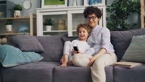 Gelukkig kind die op TV met moeder thuis bij de afstandsbediening van de bankholding letten stock footage