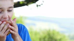 Gelukkig kind die rode appel in de lentepark eten Gezond levensstijlconcept stock footage