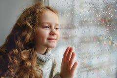 Gelukkig kind die uit het venster met natte slechte wea van de glasherfst kijken royalty-vrije stock fotografie