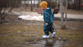 Gelukkig kind die water afstotend kostuum dragen die in een vulklei met een stok in zijn hand springen stock footage
