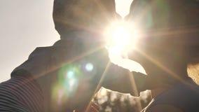 Gelukkig kind in handen van moeder Familieomhelzingen over zonsondergang stock footage