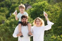 Gelukkig kind met ouders die met stuk speelgoed vleugels tegen de achtergrond van de de zomerhemel spelen Gelukkige glimlachende  royalty-vrije stock afbeelding
