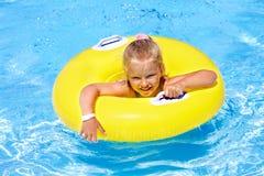 Kind op opblaasbare ring in zwembad. Stock Afbeeldingen