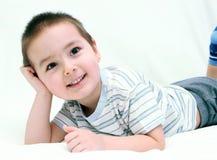 Gelukkig kind op wit bed Stock Fotografie