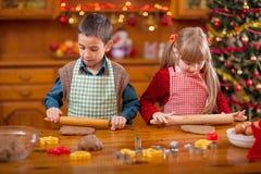 Gelukkig kind twee die koekje voor familiediner voorbereiden op Kerstmisvooravond royalty-vrije stock foto