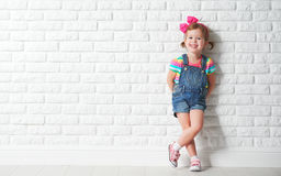 Gelukkig kindmeisje die bij lege bakstenen muur lachen Stock Foto's