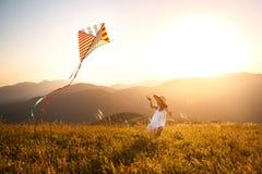 Gelukkig kindmeisje die met vlieger bij zonsondergang in openlucht lopen Stock Foto's