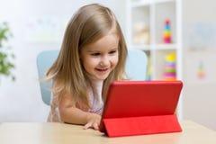 Gelukkig kindmeisje die tabletcomputer met behulp van royalty-vrije stock afbeelding