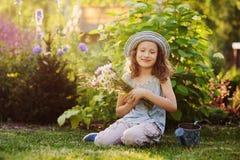 Gelukkig kindmeisje die weinig tuinman in de zomer spelen, grappige hoed dragen en boeket van bloemen houden Royalty-vrije Stock Fotografie