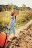 Gelukkig kindmeisje met oranje koffer die alleen op de zomervakantie reizen Jong geitje die naar de zomerkamp gaan Stock Afbeelding