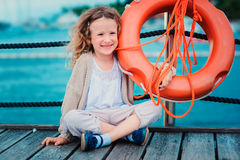 Gelukkig kindmeisje met reddingsring met overzeese achtergrond, veiligheid op het waterconcept Stock Foto's