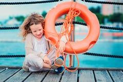 Gelukkig kindmeisje met reddingsring met overzeese achtergrond, veiligheid op het waterconcept Royalty-vrije Stock Afbeeldingen